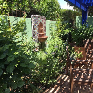 Immagine di un piccolo patio o portico eclettico dietro casa con fontane, pavimentazioni in mattoni e una pergola