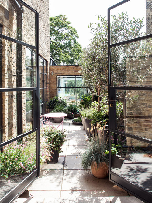 Example Of A Trendy Courtyard Concrete Paver Patio Design In London