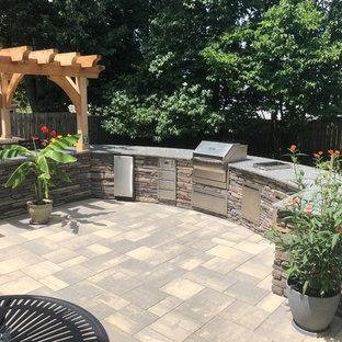 Foto di un ampio patio o portico eclettico dietro casa con pavimentazioni in mattoni e una pergola