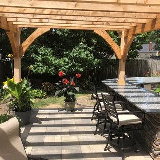 Idee per un ampio patio o portico eclettico dietro casa con pavimentazioni in mattoni e una pergola
