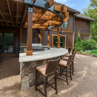 Example of a large arts and crafts backyard concrete patio kitchen design in Kansas City with a pergola