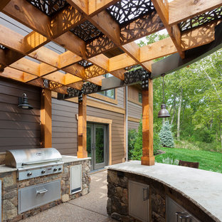Inspiration for a large traditional back patio in Kansas City with an outdoor kitchen, concrete slabs and a pergola.