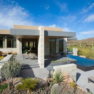 Esempio di un ampio patio o portico moderno dietro casa con un tetto a sbalzo