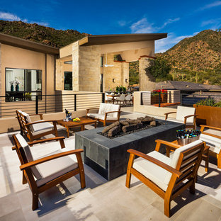 Inspiration for a large southwestern side yard stone patio remodel in Phoenix with a fire pit and no cover