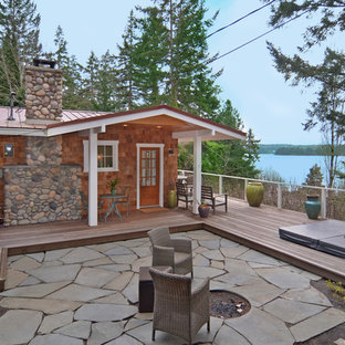 Mid-sized mountain style stone patio photo in Seattle with a fire pit and no cover