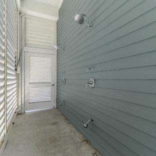 Esempio di un ampio patio o portico stile marinaro con lastre di cemento