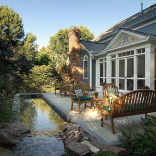 Modelo de patio tradicional, de tamaño medio, en patio trasero, con fuente y adoquines de hormigón