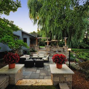 Foto di un ampio patio o portico design dietro casa con fontane e pavimentazioni in pietra naturale