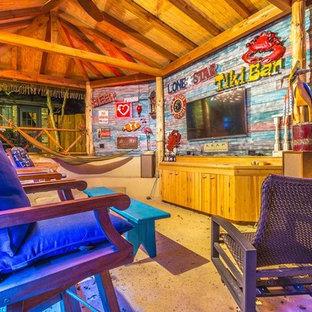 Immagine di un patio o portico tropicale di medie dimensioni e dietro casa con un gazebo o capanno