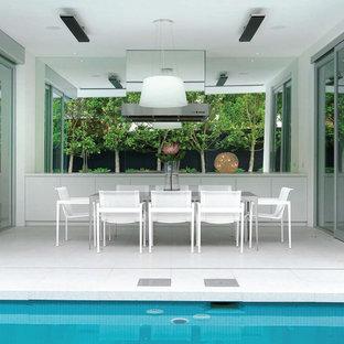 Immagine di un grande patio o portico minimalista con un tetto a sbalzo