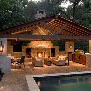 Idee per un grande patio o portico design dietro casa con un focolare, cemento stampato e un gazebo o capanno
