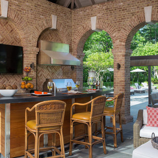 Patio kitchen - large traditional backyard stone patio kitchen idea in Other with a roof extension