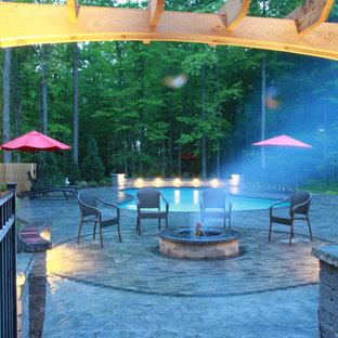 Immagine di un grande patio o portico classico dietro casa con un focolare, cemento stampato e una pergola