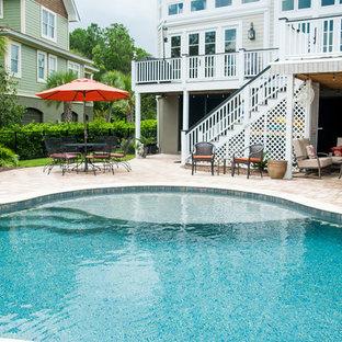 Foto di un grande patio o portico tropicale dietro casa con un focolare, pavimentazioni in pietra naturale e nessuna copertura