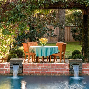 Mid-sized elegant backyard stone patio fountain photo in Houston with a pergola