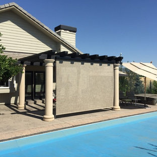 This is an example of a large traditional backyard patio in Seattle with concrete slab and a pergola.