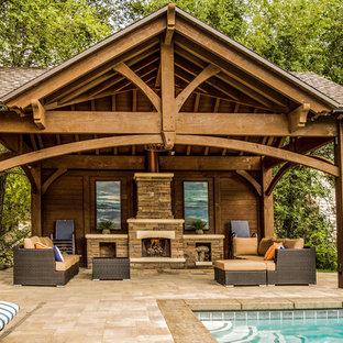 Ispirazione per un patio o portico american style di medie dimensioni e dietro casa con un caminetto, pavimentazioni in pietra naturale e un gazebo o capanno