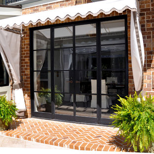 This is an example of a medium sized traditional back patio in Atlanta with brick paving and an awning.