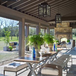 Idee per un patio o portico country dietro casa con un focolare, pavimentazioni in pietra naturale e un tetto a sbalzo
