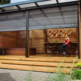 Mid-sized trendy backyard patio photo in Orange County with a roof extension and decking