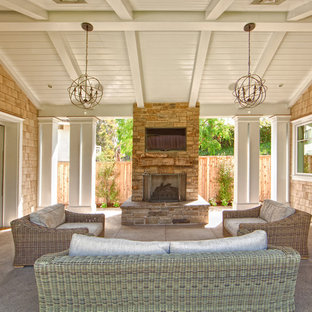 Example of a mid-sized classic courtyard concrete patio design in Orange County with a roof extension