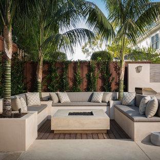 Idee per un grande patio o portico moderno dietro casa con un focolare, lastre di cemento e nessuna copertura