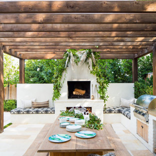 Design ideas for a traditional back patio in Orange County with a fireplace and a pergola.