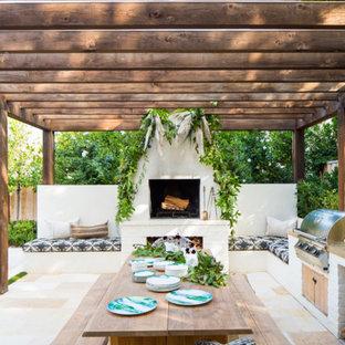 Idee per un patio o portico chic dietro casa con un caminetto e una pergola