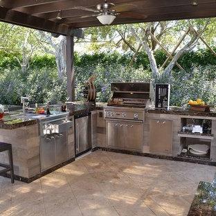 Idée de décoration pour une terrasse avec une cuisine extérieure arrière chalet de taille moyenne avec du béton estampé et une pergola.