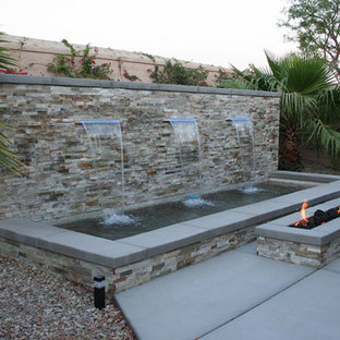 Example of a mid-sized island style backyard concrete patio fountain design in Los Angeles with no cover