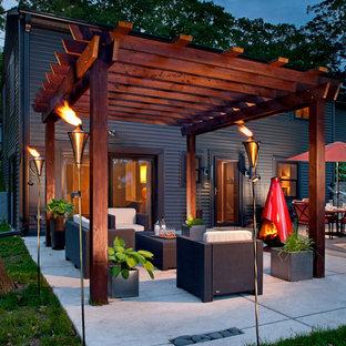 Exemple d'une terrasse arrière tendance de taille moyenne avec un foyer extérieur, une pergola et une dalle de béton.