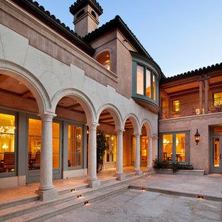 Esempio di un ampio patio o portico mediterraneo dietro casa con pavimentazioni in pietra naturale e un tetto a sbalzo