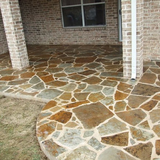 Inspiration for a mid-sized modern backyard stone patio remodel in Dallas with a roof extension
