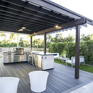 Mid-sized elegant backyard stamped concrete patio kitchen photo in Tampa with a pergola