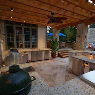 This is an example of a medium sized mediterranean back patio in Tampa with an outdoor kitchen, stamped concrete and a pergola.