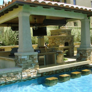 Design ideas for a medium sized mediterranean back patio in Tampa with an outdoor kitchen, stamped concrete and a pergola.