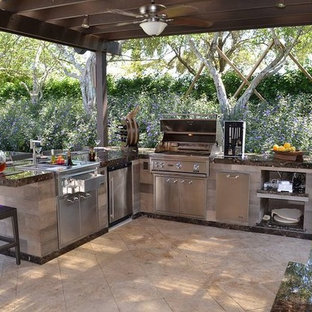 Inspiration for a mid-sized timeless backyard stamped concrete patio kitchen remodel in Tampa with a pergola