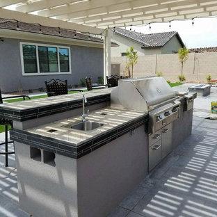 Idee per un patio o portico tradizionale di medie dimensioni e dietro casa con pavimentazioni in cemento e una pergola