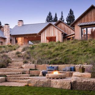 Esempio di un patio o portico country con pavimentazioni in pietra naturale e un focolare