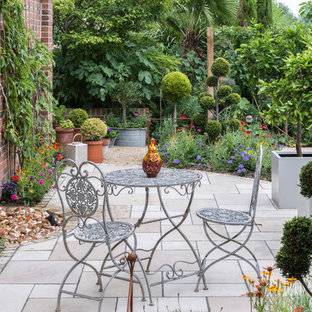 This is an example of a mid-sized traditional side yard patio in Berkshire with a water feature, concrete pavers and no cover.