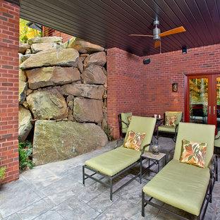 Foto di un grande patio o portico american style dietro casa con fontane, cemento stampato e un tetto a sbalzo