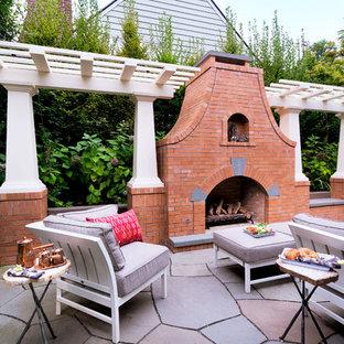 Immagine di un patio o portico chic di medie dimensioni con pavimentazioni in pietra naturale, una pergola e un caminetto