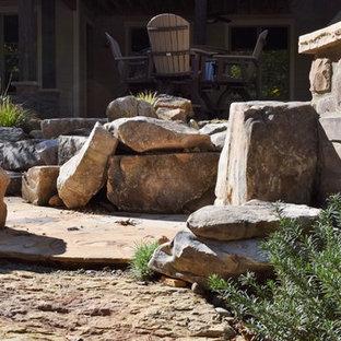 Immagine di un patio o portico rustico di medie dimensioni e dietro casa con un focolare, pavimentazioni in pietra naturale e una pergola