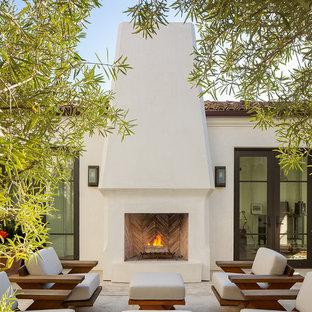 Unbedeckter Mediterraner Patio hinter dem Haus mit Kamin und Betonplatten in San Diego