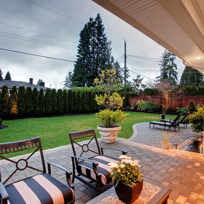 Example of a trendy concrete paver patio design in Vancouver with a roof extension