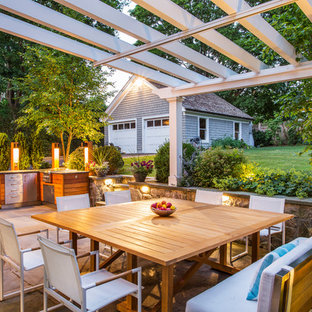 Example of a mid-sized classic backyard stone patio kitchen design in New York with a pergola