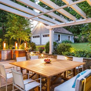 Imagen de patio tradicional, de tamaño medio, en patio trasero, con adoquines de piedra natural y pérgola