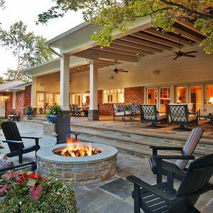 This is an example of an expansive classic back patio in Dallas with a fire feature, natural stone paving and a roof extension.