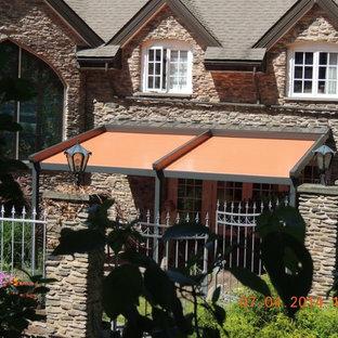 Mid-sized elegant backyard stone patio photo in Miami with a pergola