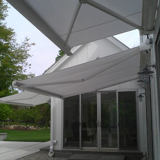Example of a mid-sized trendy backyard stone patio design in New York with an awning